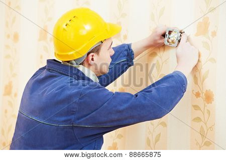 electrician worker at electric wall outlet or light switch socket installation work