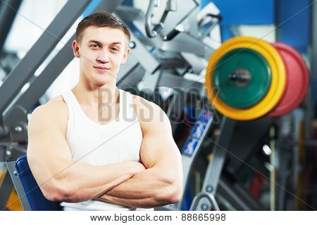 Portrait of a smiling male trainer standing in the gym
