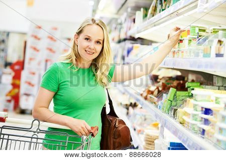 Shopping woman choosing bio food products in dairy store or supermarket shop