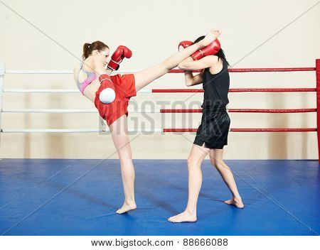 muai thai women fighting at training boxing ring