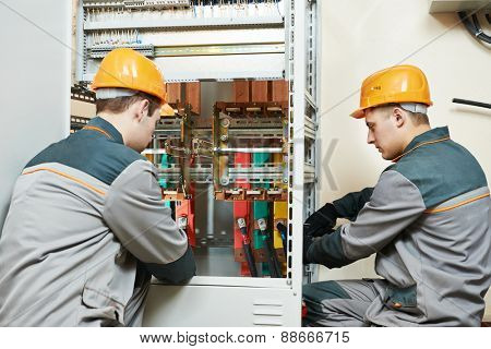 electrician builder engineer workers with electric cable wiring of fuse switch box