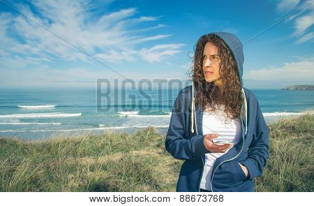 Young woman with hoodie and sportswear holding smartphone