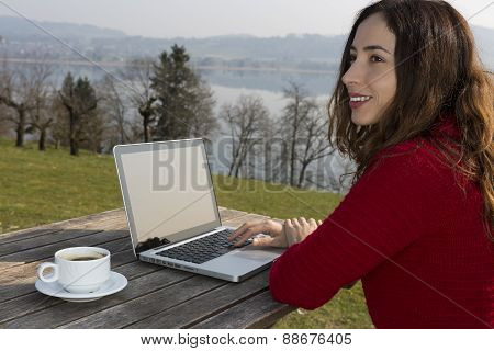Woman With Her Laptop And A Cup Of Coffee At A Restaurant