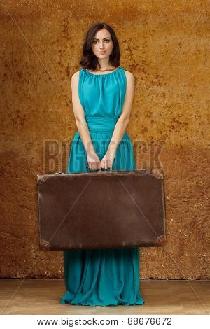 Woman in blue dress with suitcase