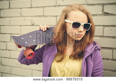 Nice Blond Teenage Girl In Sunglasses Holds Skateboard