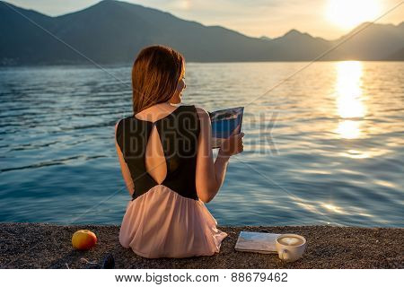 Young woman sitting on the pier at sunrise