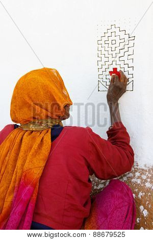 Senior indian lady in sari dress decorates the wall of a house with paint