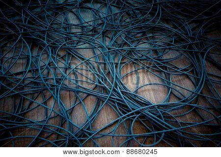 Network chaos of colorful cables on the wooden floor.
