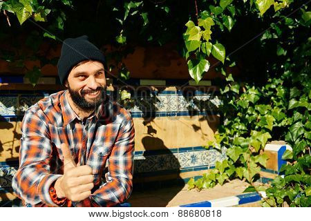 Portrait Of Smart Smiling Man Giving You Thumb Up And Looking Up At Green Plants Background.