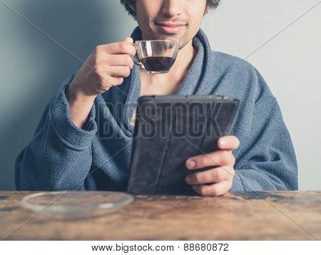 Man In Bathrobe Having Coffee And Using Tablet