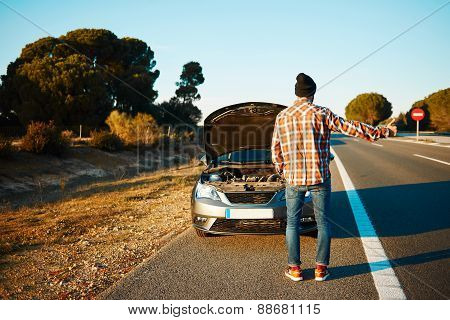 Yong caucasian man trying stop cars in travel because his car broken down.