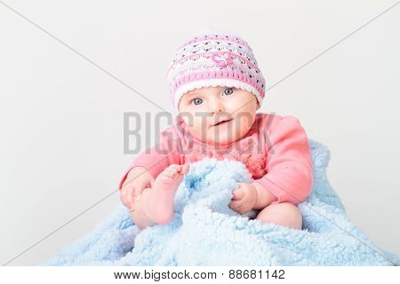 Little Smiling Baby Girl Sitting On Blanket