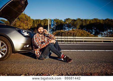 Young Brutal Caucasian Male Looking At Camera. Sits Near Car Talking On Cell Phone