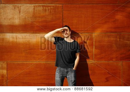 Hipster Standing On City Wall Keeps The Hand From The Head Blocks Sunlight In His Big Blue Eyes.