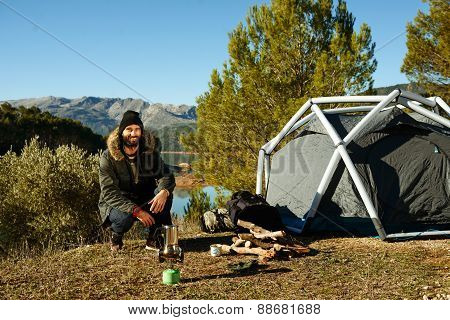 Hiking People. Adventure Man Camping Waits To Make Coffee On A Gas Stove When Traveling Outdoors