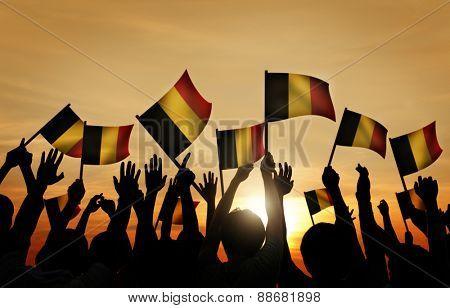 Group of People Waving Belgian Flags in Back Lit