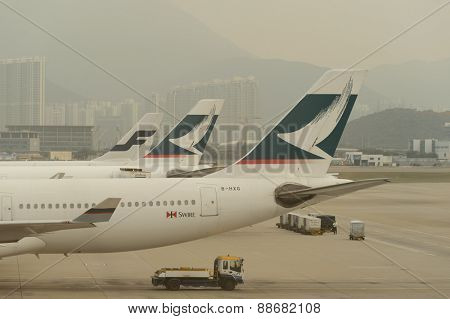 HONG KONG - MARCH, 09, 2015: Cathay Pacific aircraft near boarding bridge. Cathay Pacific is the flag carrier of Hong Kong, with its head office and main hub located at Hong Kong International Airport