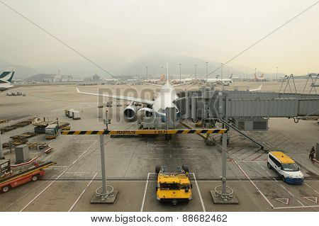 HONG KONG - MARCH 09, 2015: Cathay Pacific aircraft near boarding bridge. Cathay Pacific is the flag carrier of Hong Kong, with its head office and main hub located at Hong Kong International Airport