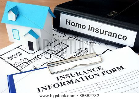 Model of house and folder with home insurance.