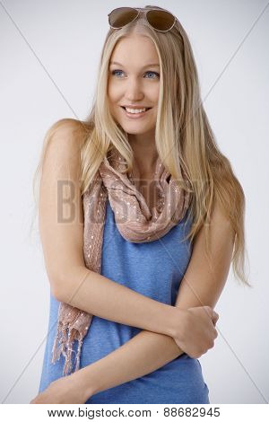 Summer portrait of beautiful young blonde woman smiling, looking away.