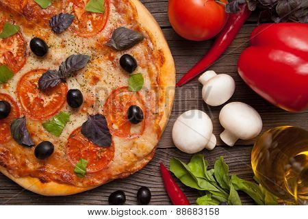 Pizza margherita with tomatoes, olives and basil on vintage rust