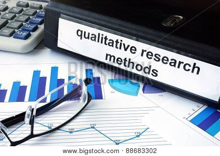 File folder with words words qualitative research methods and financial graphs.