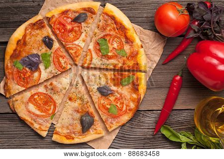 Sliced traditional italian pizza margherita with tomatoes, olive