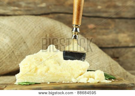 Cheese with blade on wooden table with sackcloth, closeup