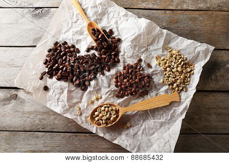 Coffee beans on crumpled parchment on wooden table, top view
