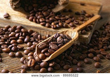 Coffee beans on wooden table, closeup