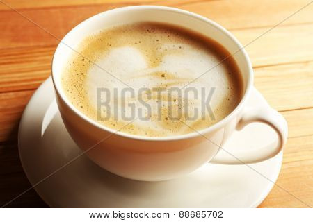 Cup of coffee latte art on wooden table, closeup