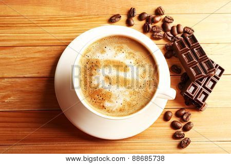 Cup of coffee latte art with grains and chocolate on wooden table, top view
