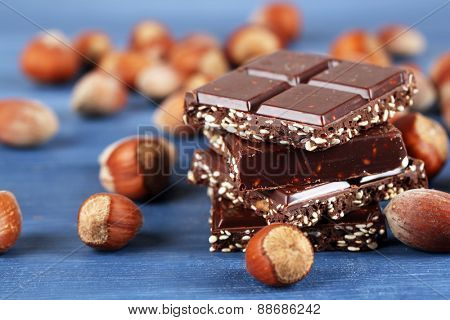 Pieces of chocolate with hazelnut on wooden table, closeup