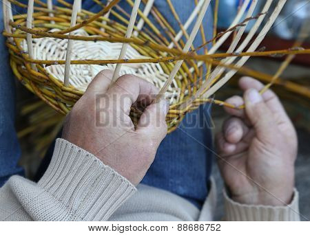 Expert Hands Of Craftsman Creates A Woven Wicker Basket