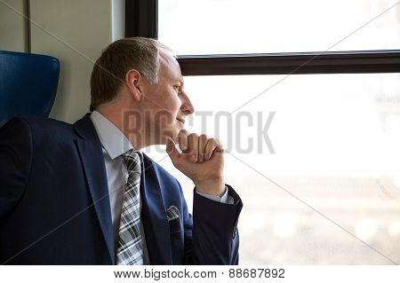 Businessman Interested In What He Sees Through Window