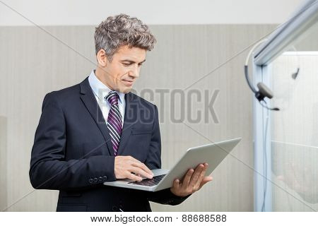Mid adult business executive using laptop at call center