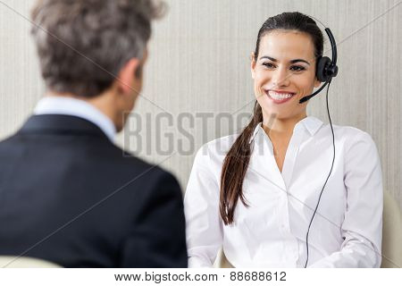 Happy female customer service representative wearing headset while looking at manager in office
