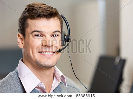 Closeup portrait of confident male customer service representative with headset in office