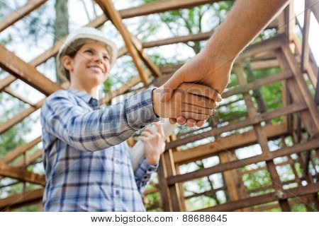 Low angle view of smiling female architect greeting male colleague at construction site