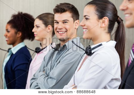 Portrait of happy male call center employee standing in row with colleagues at office