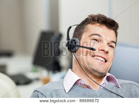 Smiling customer service representative wearing headset while looking away in office