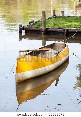 Empty canoe moored in calm lake