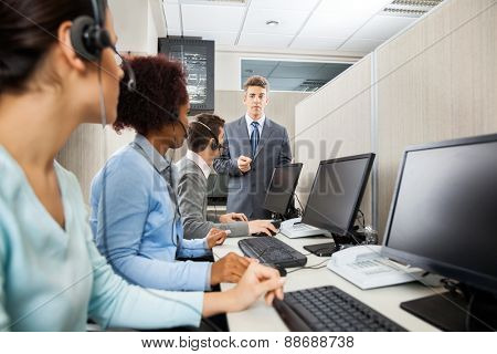 Confident manager in discussion with customer service representatives in office