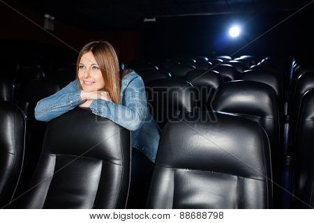 Beautiful woman leaning on seat while watching movie at cinema theater