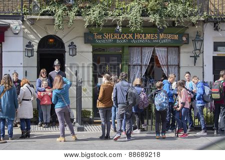 LONDON, UK - APRIL 22: Tourists pose with actor dressed in traditional British police uniform at the entrance of the Sherlock Holmes museum. April 22, 2015 in London.
