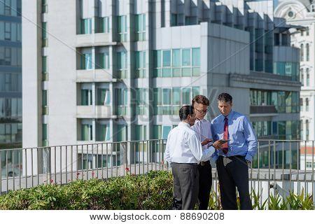 Businessmen discussing information on digital tablet