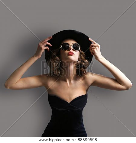 Expressive young model with hat and sunglasses on gray background