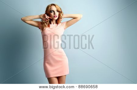 Beautiful young woman in pink dress posing on light blue background