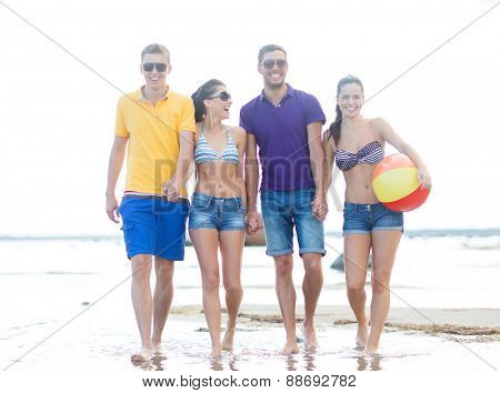 summer holidays, vacation, tourism, travel and people concept - group of happy friends with inflatable ball walking along beach