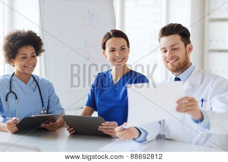 hospital, profession, people and medicine concept - group of happy doctors with tablet pc computers meeting at medical office